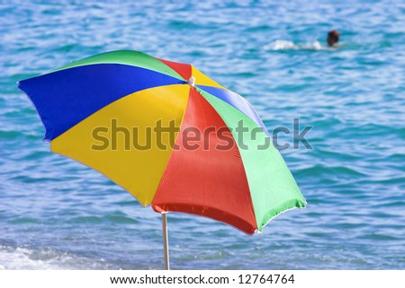bright funny colored beach umbrella on a background of a sea waves - stock photo