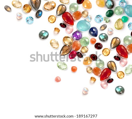 Bright gemstones on the white background. Mix of real gems: labradorite, citrine, garnet, amazonite, ruby, garnet, amethyst, jade, chalcedony, blue topaz, moonstone rainbow, peach moonstone and more.. - stock photo