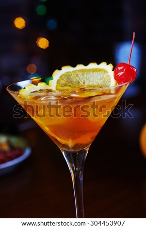 bright glass of delicious alcoholic cocktail or lemonade with ice and a slice of orange on a table in a bar or restaurant with decor and beautiful bokeh in the background. soft focus. - stock photo