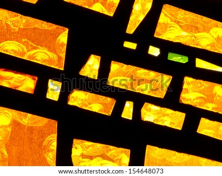 Bright gold and yellow abstract stained glass window design in modern parish church - stock photo