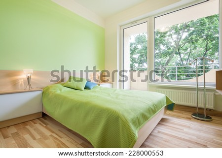 Bright green bedroom with big double bed - stock photo