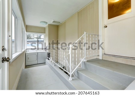 Bright hallway with stairs to basement. View of small laundry area - stock photo