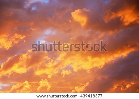 Bright heavenly sunset golden and purple light sky background. Idyllic beautiful sky with thunderclouds. - stock photo