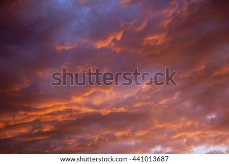 Bright heavenly sunset golden and purple light sky background. Idyllic beautiful sky with thunderclouds. Dramatic sunset with golden clouds - stock photo