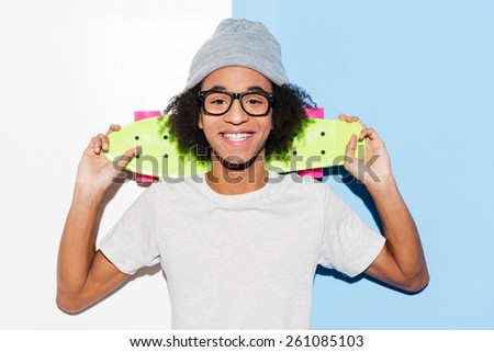 Bright hobby. Handsome young African man carrying skateboard on his shoulders while standing against colorful background  - stock photo