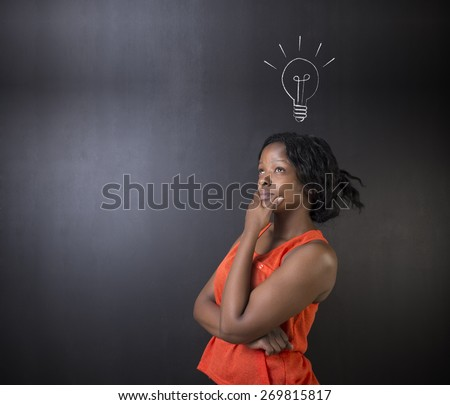 Bright idea chalk background lightbulb thinking South African or African American woman teacher or student - stock photo
