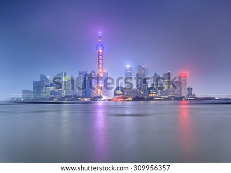 bright illuminated Shanghai's Pudong district at sunset from the Bund across the river reflecting in still water - stock photo