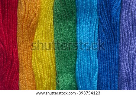 Bright iridescent thread floss for embroidery and needlework. Sewing threads for embroidery close-up. Multicolor sewing threads texture. Mouline.  - stock photo