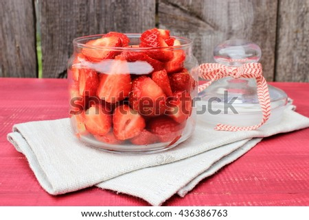 Bright kitchen decor elements in red color: fine glass top with tasty ripe strawberry on grey linen napkin. Red and grey color.  - stock photo