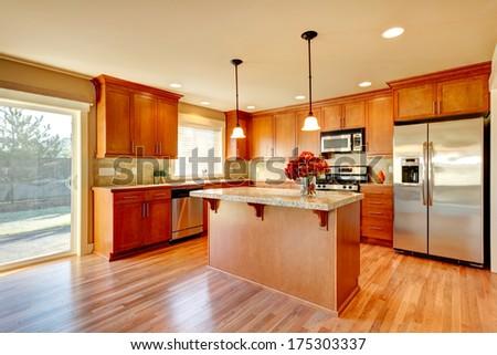 Bright kitchen with hardwood floor, wood cabinets, modern steel appliances and tile back splash - stock photo