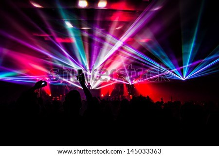 bright laser show in the crowd of merry men - stock photo