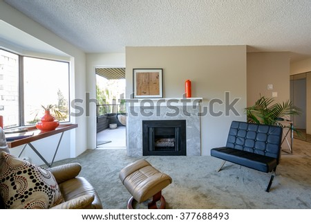 Bright living room seating area with leather chairs, coffee table, and fireplace. Interior design. - stock photo