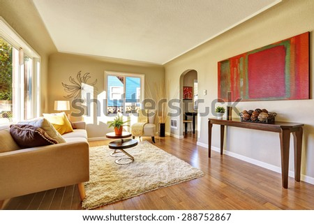 Bright living room with hardwood floor and tan sofa. - stock photo