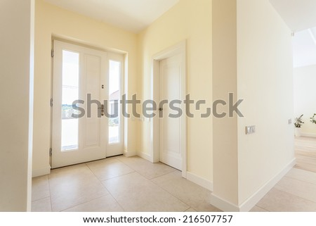 Bright lobby with big front door in modern house - stock photo