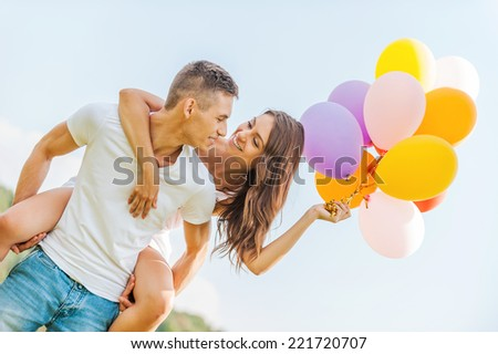 Bright love. Low angle view of young man carrying beautiful cheerful girl with colorful balloons on his shoulders - stock photo
