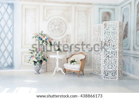 Bright luxury white and blue colored interior living room with flowers in vases. the walls are decorated with baroque ornaments - stock photo