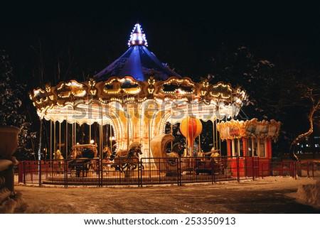 bright merry-go-round at dark night in winter - stock photo