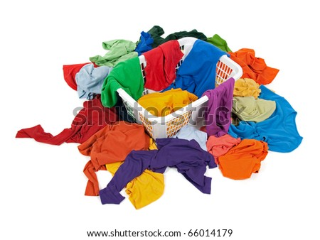 Bright messy clothes in a laundry basket and around it. Isolated on white background. - stock photo