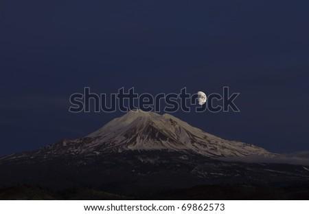 Bright moon over Mount Shasta at dusk - stock photo