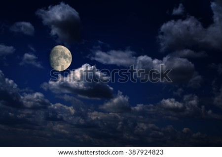 Bright moon over scattered clouds at night - stock photo