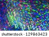 Bright multi-colored background from being poured strips of light. Photo of multi-colored Christmas tree decorations removed in movement. - stock photo