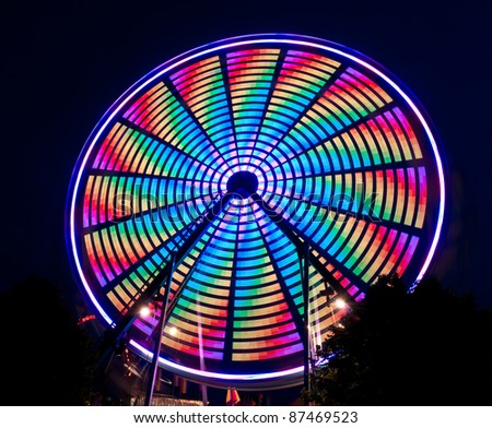 Bright Multi-Colored Spinning Ferris Wheel - patterns created by lights on wheel - stock photo