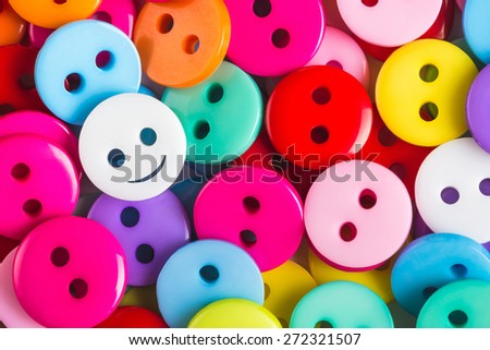 bright multicolored buttons of red, yellow, blue, orange, pink color, among them the white button - smiley stands out among other, top view,  background - stock photo