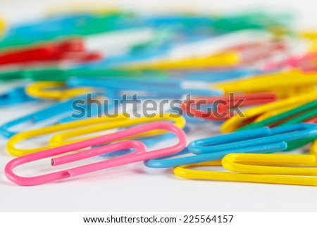 Bright multicolored office paperclips on white desktop close up - stock photo