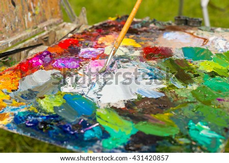 Bright multicolored palette of blended oil paints with one professional paintbrush in the garden - stock photo