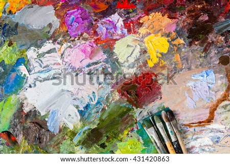 Bright multicolored palette of blended oil paints with paintbrushes - stock photo