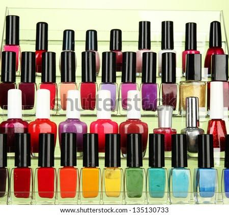Bright nail polishes on shelf on green background - stock photo