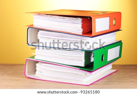 bright office folders on wooden table on yellow background - stock photo