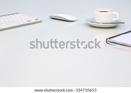 Bright Open Space Office White Table Angle View with Coffee Mug Opened Blank Notepad and Computer Keyboard and Mouse on Desk Side View with Reflections and Copy Space - stock photo