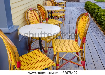 Bright orange and red plastic wicker bistro chairs surround white table outside a coffee shop. - stock photo