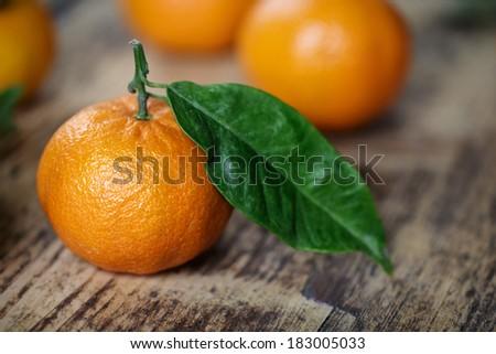 Bright Orange Mandarin with Green Leaf on Rustic Wooden board - stock photo