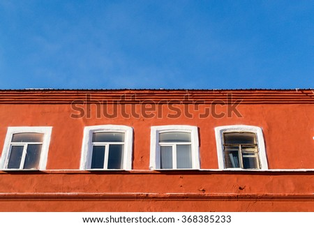 Bright orange painted aged building with four white windows set against a bright blue summer sky. Architectural image details with nobody and copy space. - stock photo