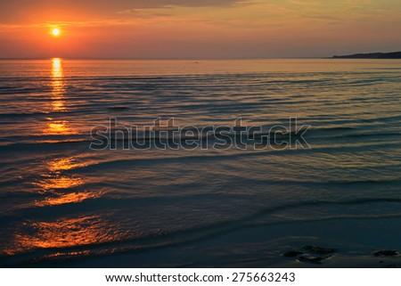 Bright orange sunset at the sea with sun - stock photo