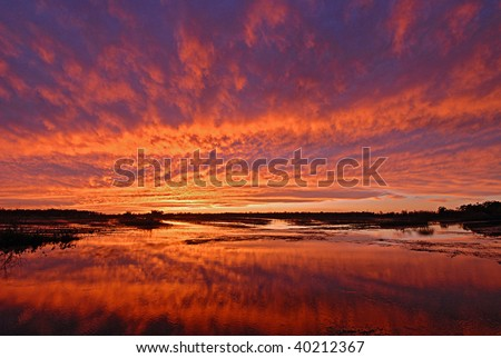 Bright orange sunset sky reflect in marsh wetland in Louisiana - stock photo
