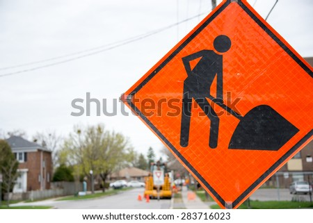 Bright orange traffic sign warns of construction ahead with construction equipment in the background. - stock photo