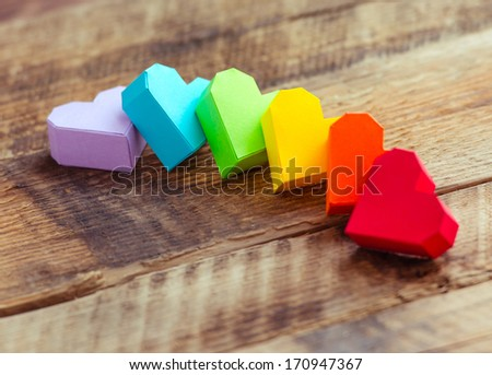Bright paper hearts on wooden background - stock photo
