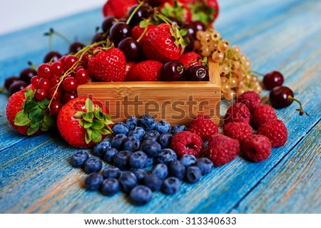 Bright picture from the kitchen Italian chef who makes the best dessert  from ripe fresh berries, berries, he served in a wooden cookware - stock photo