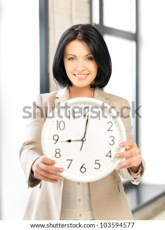 bright picture of attractive businesswoman with clock - stock photo