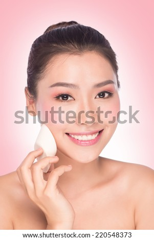 bright picture of beautiful asian woman applying foundation.  - stock photo