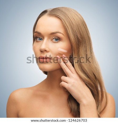 bright picture of beautiful woman applying foundation. - stock photo