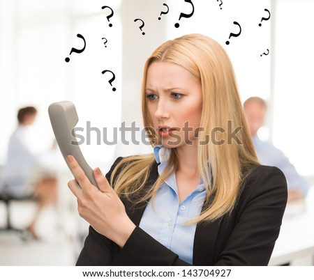 bright picture of confused woman with phone in office - stock photo