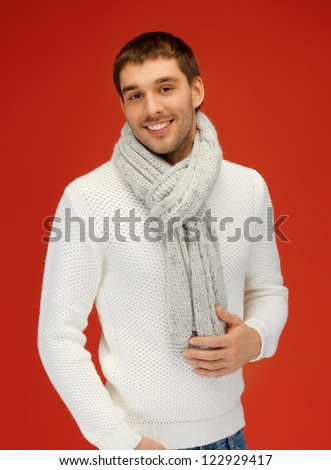 bright picture of handsome man in warm sweater and scarf. - stock photo