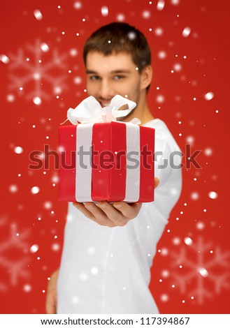 bright picture of handsome man with a gift (focus on box) - stock photo