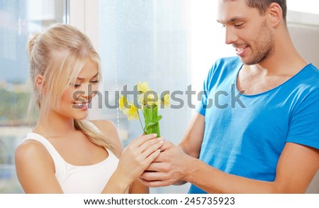 bright picture of happy romantic couple with flowers, focus on woman - stock photo