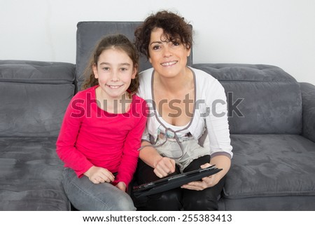 bright picture of hugging mother and daughter looking at tablet - stock photo