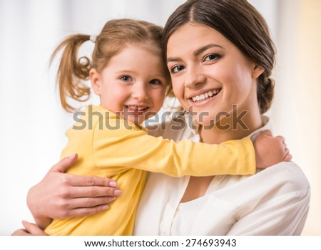 Bright picture of hugging mother and little daughter. - stock photo